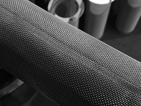 Spot roll welding seam of cylindrical wire mesh filter cartridge, background are mesh filter baskets