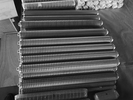 Dozens of sintered metal fiber felt filter cartridges on a cart, with square hole perforated metal outer protection sleeve