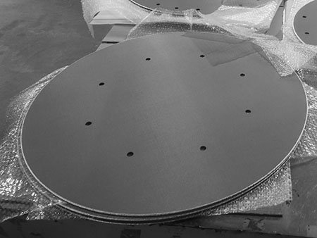 Sintered metal mesh filter disc for chromatography column with several holes for installation and sealing.