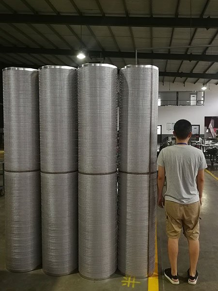 Several sintered metal mesh filter tube & screen for automatic self-cleaning filter standing in Lianda filter's workshop, an employee for size comparison