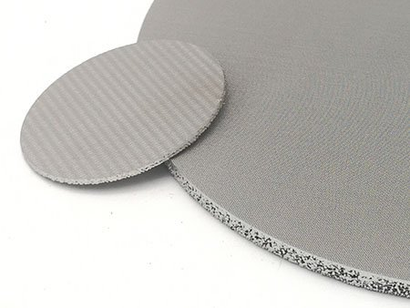 Small round piece sintered wire mesh disc lay on a bigger and thicker sintered mesh disc