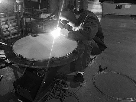 Lianda Filter employee sitting and welding the sintered wire mesh filter disc with TIG welding