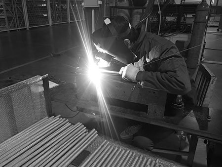 Lianda Filter employee sitting and welding the sintered wire mesh filter tube, there are dozens of finished tubes in front cart