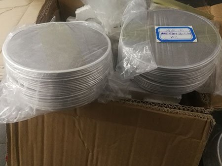 Two stacks of stamped rim pack wire mesh discs in plastic bags